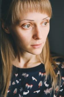 Portret van een jonge vrouw die weg kijkt.