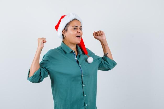 Portret van een jonge vrouw die winnaargebaar in overhemd, kerstmuts toont en er gelukkig vooraanzicht uitziet