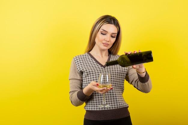 Portret van een jonge vrouw die witte wijn in het glas giet.