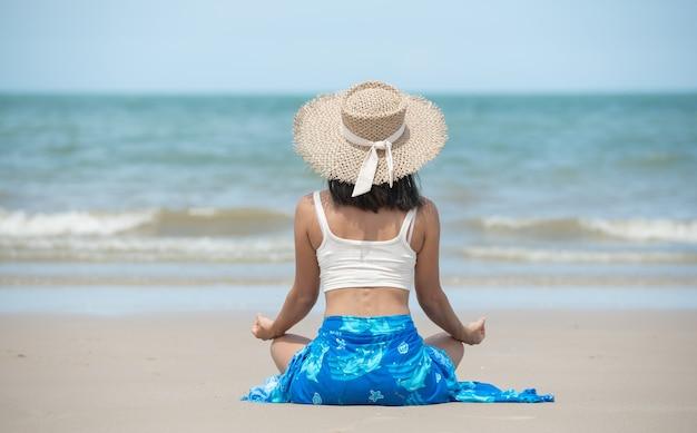 Portret van een jonge vrouw die yoga beoefent in de zomeromgeving met hoed, zonnebril