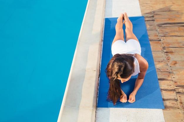 Portret van een jonge vrouw die yoga-oefeningen buitenshuis maakt