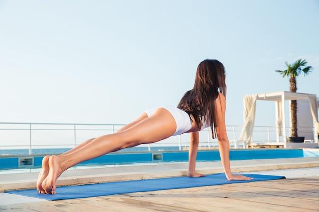 Portret van een jonge vrouw die yoga-oefeningen op yogamat buitenshuis maakt