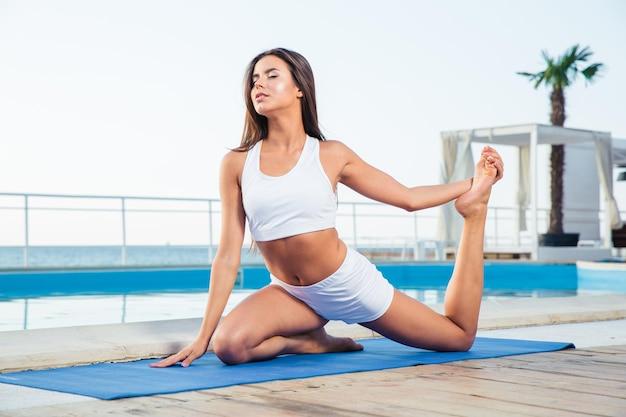 Portret van een jonge vrouw die yogaoefeningen buitenshuis doet