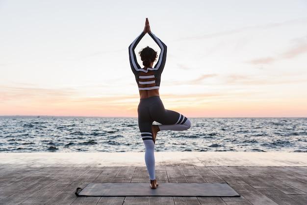 Portret van een jonge vrouw die yogaoefeningen doet