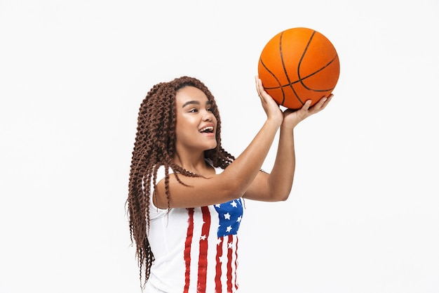 Portret van een jonge vrouw die zich verheugt en basketbal vasthoudt tijdens het spel terwijl ze geïsoleerd tegen een witte muur staat