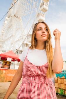 Portret van een jonge vrouw die zich voor reuzeferriswiel bevindt