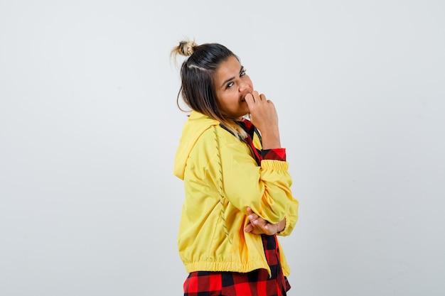Portret van een jonge vrouw die zich voordeed terwijl ze in een geruit overhemd, een jas staat en er vrolijk vooraanzicht uitziet