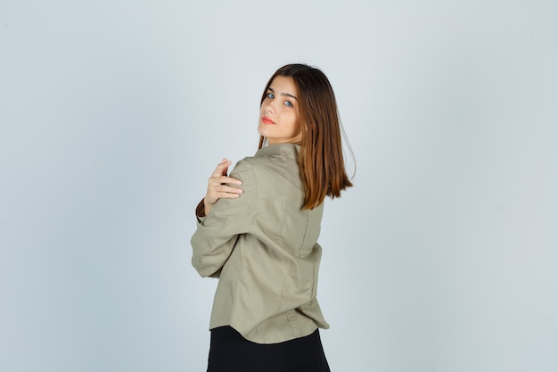 Portret van een jonge vrouw die zich voordeed terwijl ze terugkijkt in hemd, rok en er charmant uitziet aan de achterkant