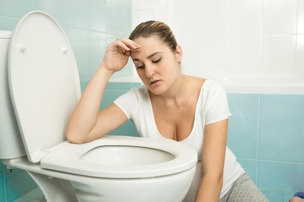 Portret van een jonge vrouw die zich ziek voelt en op het toilet leunt