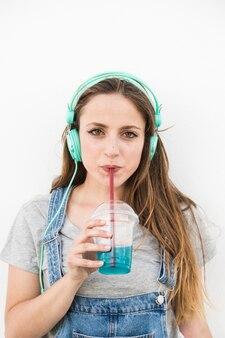 Portret van een jonge vrouw dragen hoofdtelefoon drinken sap met stro