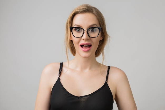 Portret van een jonge vrouw geïsoleerd op wit bril dragen in zelfverzekerde houding en zwarte jurk dragen