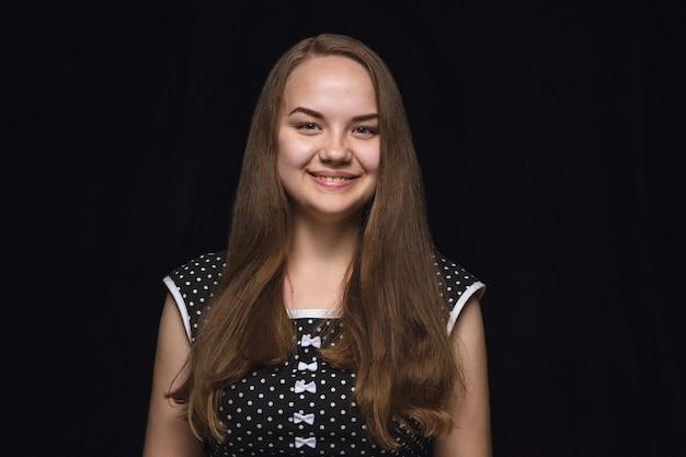 Portret van een jonge vrouw geïsoleerd op zwarte muur close-up. echte emoties van vrouwelijk model. glimlachen, zich gek gelukkig voelen, lachen. gelaatsuitdrukking, concept van menselijke emoties.