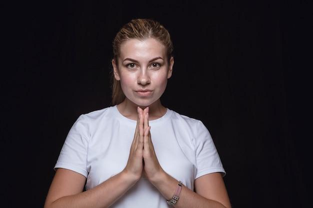 Portret van een jonge vrouw geïsoleerd op zwarte muur close-up