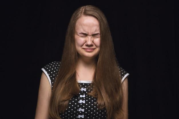 Portret van een jonge vrouw geïsoleerd op zwarte studio achtergrond close-up. photoshot van echte emoties van vrouwelijk model. huilen met gesloten ogen, verdrietig en hopeloos. gelaatsuitdrukking, concept van menselijke emoties.
