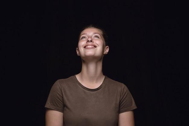 Portret van een jonge vrouw geïsoleerd op zwarte studio achtergrond close-up.