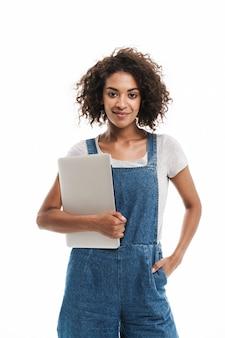 Portret van een jonge vrouw gekleed in een denim overall glimlachend en met een laptop geïsoleerd over een witte muur