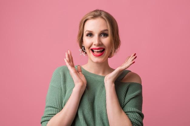 Portret van een jonge vrouw, gekleed in een groene trui met rode lippen op roze close-up