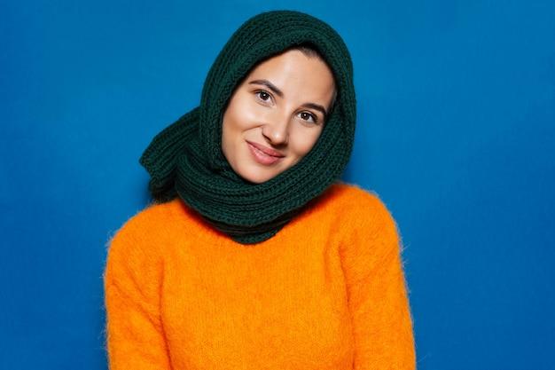 Portret van een jonge vrouw, gekleed in oranje trui en groene sjaal
