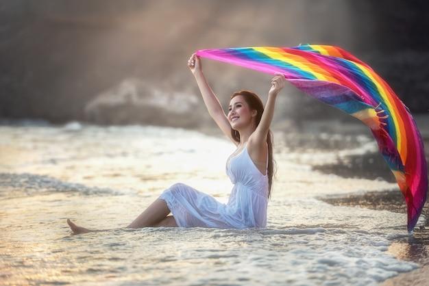 Portret van een jonge vrouw, gekleed in witte jurk met een heldere regenboog sarong ontspannen