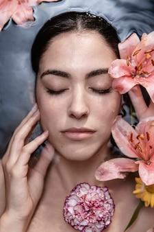 Portret van een jonge vrouw genieten van bloemenbehandeling