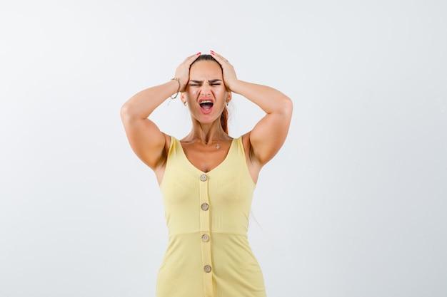 Portret van een jonge vrouw hand in hand op het hoofd in gele jurk en op zoek weemoedig vooraanzicht