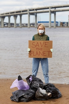 Portret van een jonge vrouw in beschermend masker met aanplakbiljet red de planeet terwijl je in de buurt van de kustlijn staat met vuilniszakken