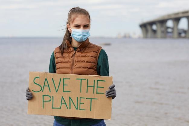 Portret van een jonge vrouw in beschermend masker met plakkaat save the planet terwijl je in de buurt van de zee staat