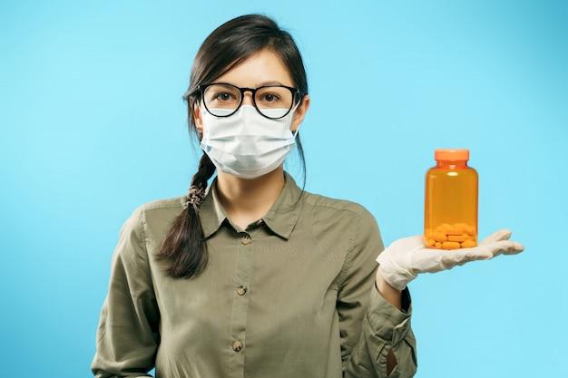 Portret van een jonge vrouw in beschermend medisch masker en handschoenen die een oranje fles met pillen of vitaminen op blauw houden.