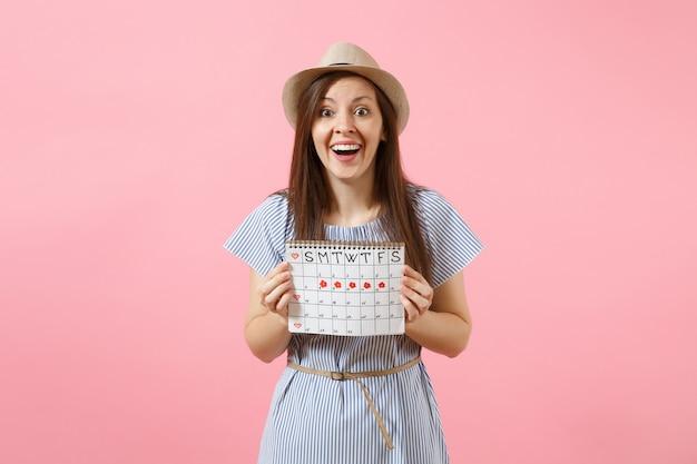 Portret van een jonge vrouw in blauwe jurk, hoed met periodenkalender voor het controleren van menstruatiedagen geïsoleerd op heldere trending roze achtergrond. medisch, gezondheidszorg, gynaecologisch concept. ruimte kopiëren.