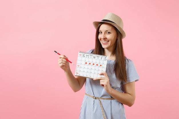 Portret van een jonge vrouw in blauwe jurk, hoed met rood potlood, vrouwelijke periodenkalender voor het controleren van menstruatiedagen geïsoleerd op roze achtergrond. medische gezondheidszorg, gynaecologisch concept. ruimte kopiëren