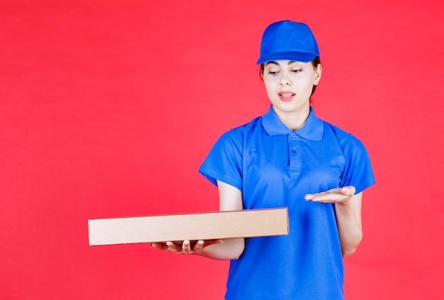 Portret van een jonge vrouw in blauwe outfit poseren met kartonnen doos over rode muur.