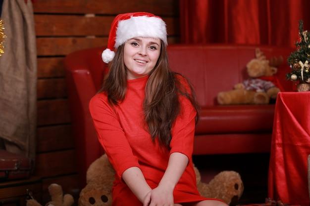 Portret van een jonge vrouw in de advertentie rode kleding van de kersthelperhoed ter voorbereiding op kerstmis thuis.
