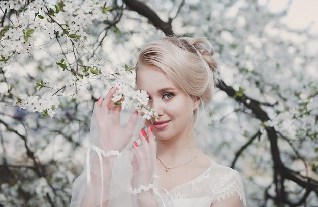 Portret van een jonge vrouw in de bloementuin in het voorjaar