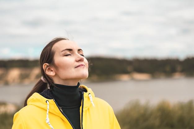 Portret van een jonge vrouw in de natuur in een gele jas die frisse, schone, koele herfstlucht ademt