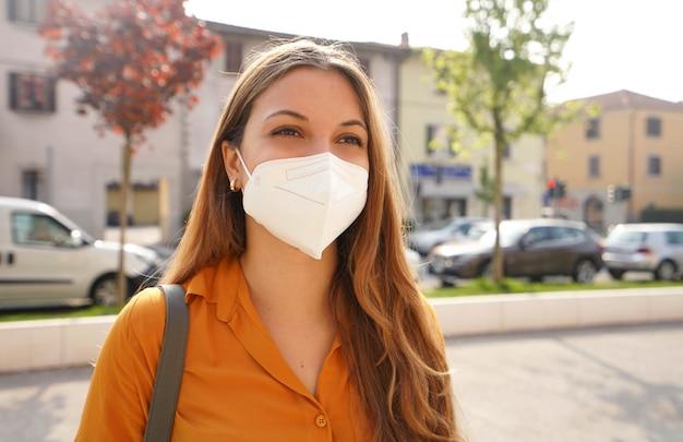 Portret van een jonge vrouw in de stadsstraat die een kn95 ffp2-masker draagt dat beschermt tegen de verspreiding van het ziektevirus sars-cov-2. meisje met beschermend masker op gezicht tegen de ziekte van coronavirus 2019.