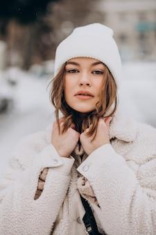 Portret van een jonge vrouw in de winteruitrusting buiten de straat