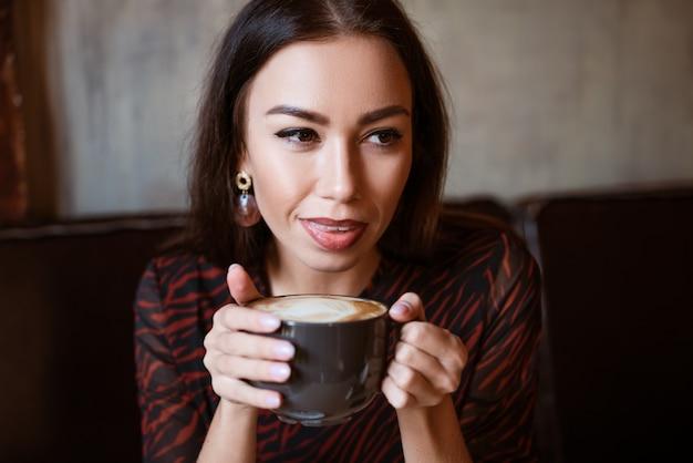 Portret van een jonge vrouw in een café met een kopje koffie