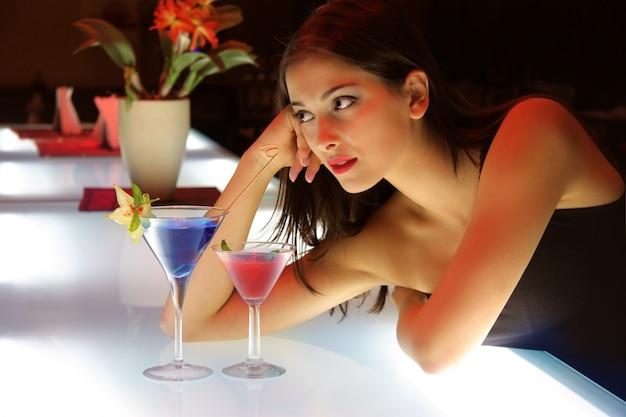 Portret van een jonge vrouw in een cocktailbar