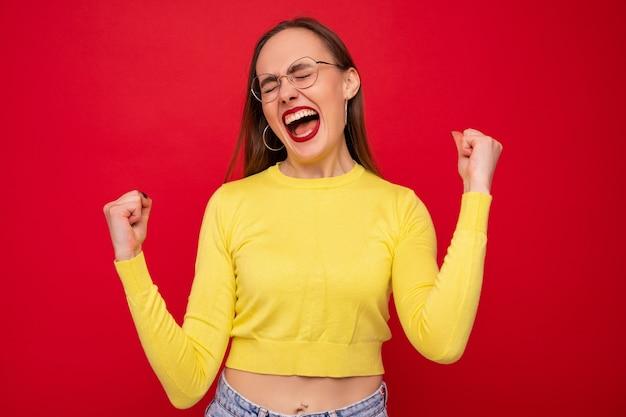 Portret van een jonge vrouw in een gele jas in een goed humeur