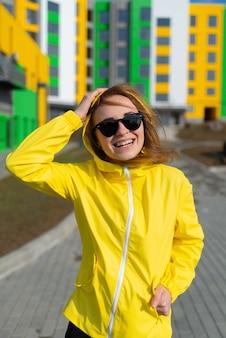 Portret van een jonge vrouw in een gele jas met een zonnebril die lacht met heldere gebouwen op de achtergrond