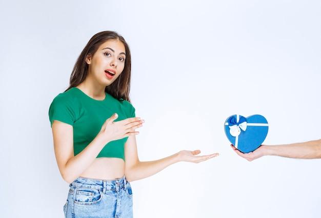 Portret van een jonge vrouw in een groen shirt die een blauwe geschenkdoos van iemand ontvangt.