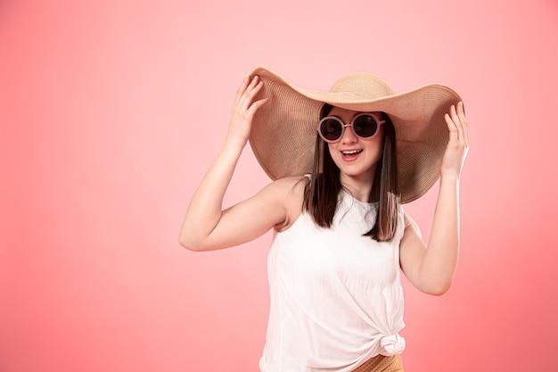 Portret van een jonge vrouw in een grote zomerhoed en bril, op een roze achtergrond. het concept van de zomer.
