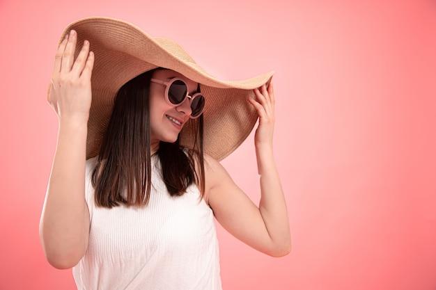 Portret van een jonge vrouw in een grote zomerhoed en bril op roze