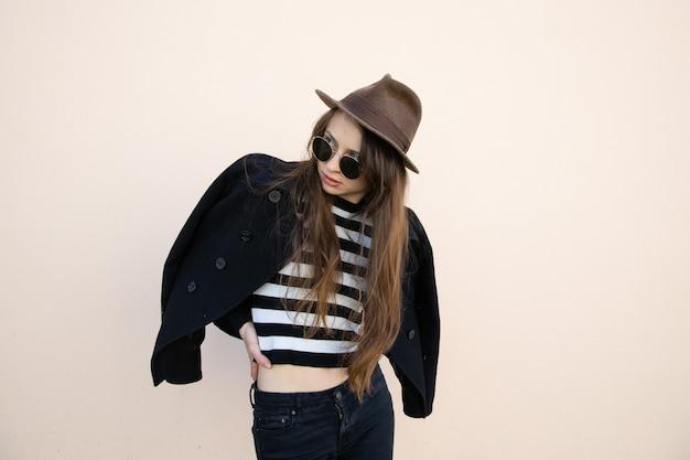 Portret van een jonge vrouw in een jas, bril en hoed poseren tegen een muur op straat