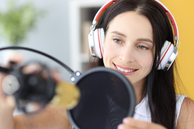 Portret van een jonge vrouw in een koptelefoon voor de microfoon