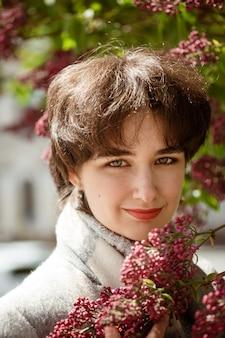 Portret van een jonge vrouw in een lila struik op een zonnige lentedag