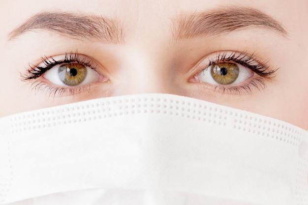 Portret van een jonge vrouw in een medisch masker. bescherming tegen virussen