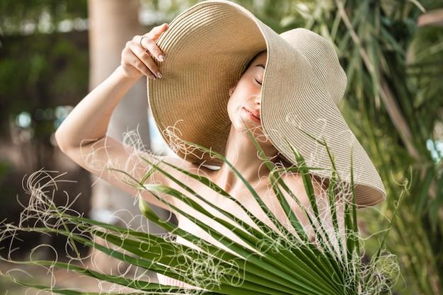 Portret van een jonge vrouw in een mooie hoed en palmblad.