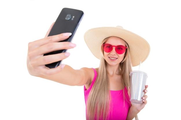 Portret van een jonge vrouw in een roze zwembroek en hoed die een glas houdt en een selfie neemt