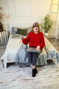 Portret van een jonge vrouw in een trui, met behulp van een laptop en een creditcard, thuis op het bed zitten, online winkelen, internetbankieren. thuis winkelen